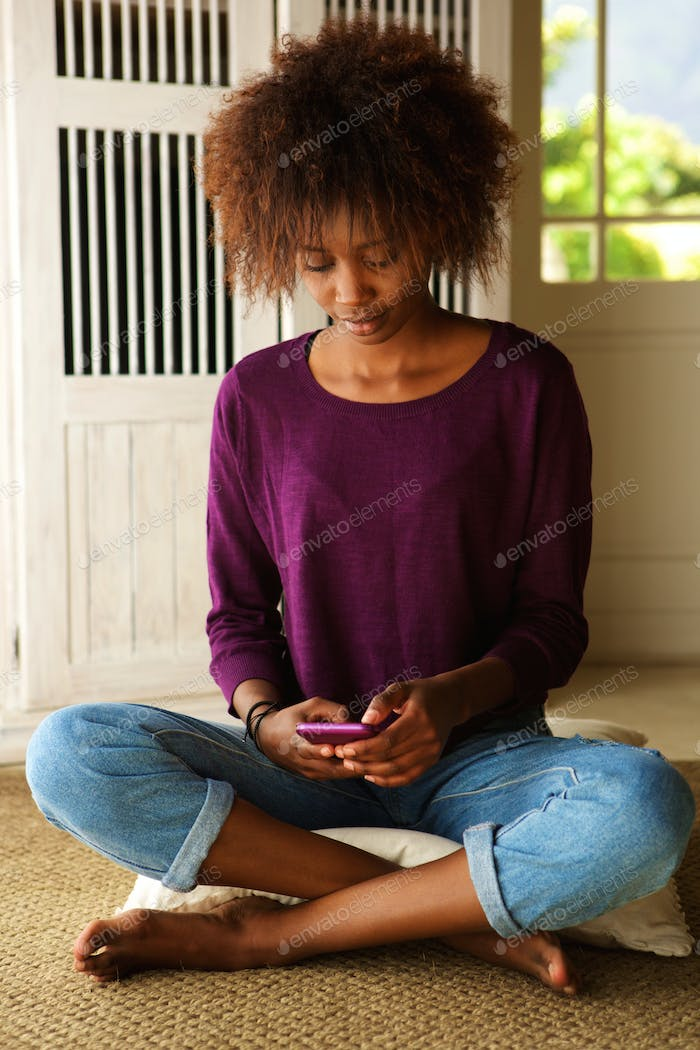 Young woman sitting on floor with mobile phone