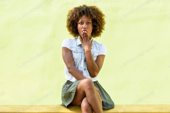 Black woman, afro hairstyle, sitting with a surprise face