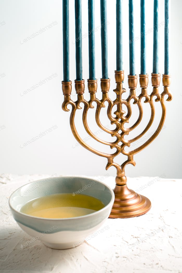Menorah brass Hanukkah with blue candles and butter in bowl side view