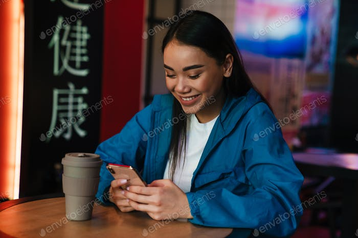 Photo of asian woman using mobile phone while sitting in cafe