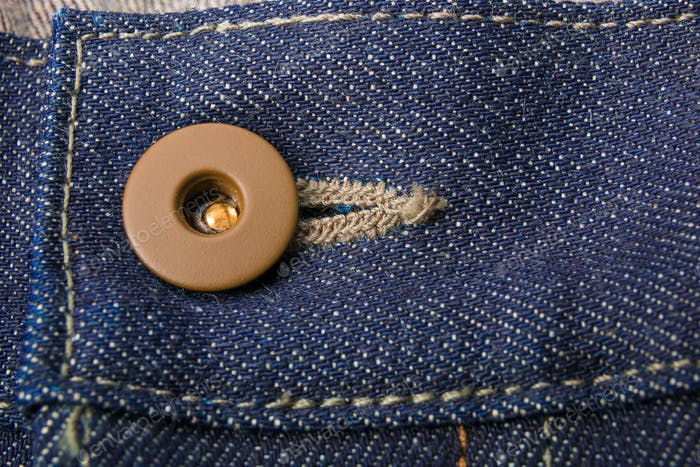 Close up of jeans fragment with button. Denim texture.