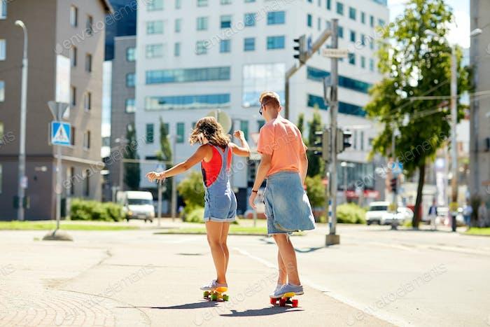 teenage couple riding skateboards on city street