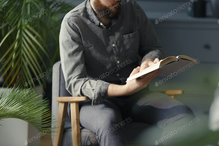 Close-up of man reading book while sitting on grey armchair