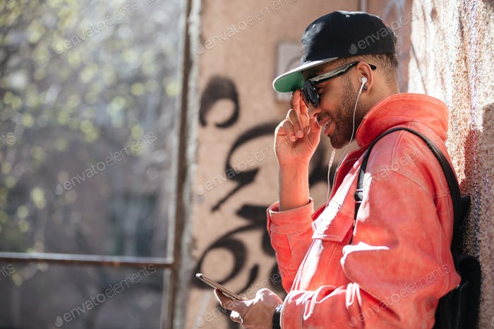 Happy stylish afro american man in sunglasses listening music