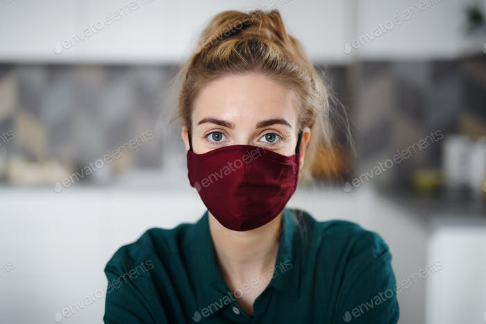 Portrait of young woman with face mask indoors at home