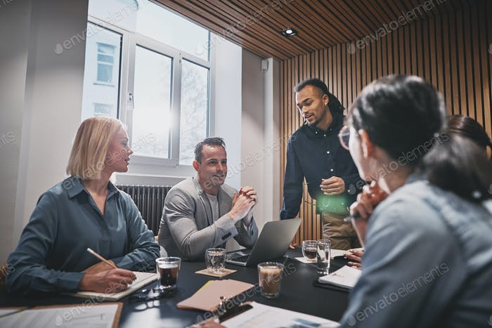 Smiling businesspeople discussing work together during a boardroom meeting