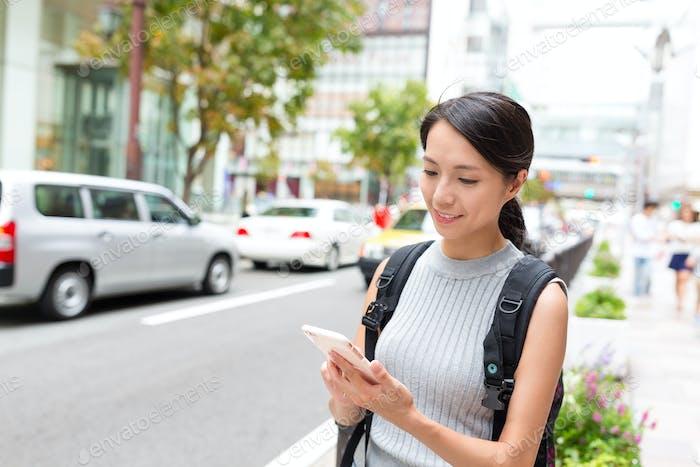 Woman checking GPS on cellphone in Fukuoka city