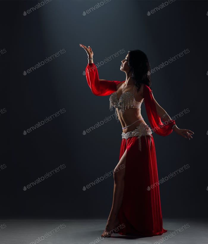 beautiful black-haired girl in red ethnic dress dancing oriental dances on stage in the dark