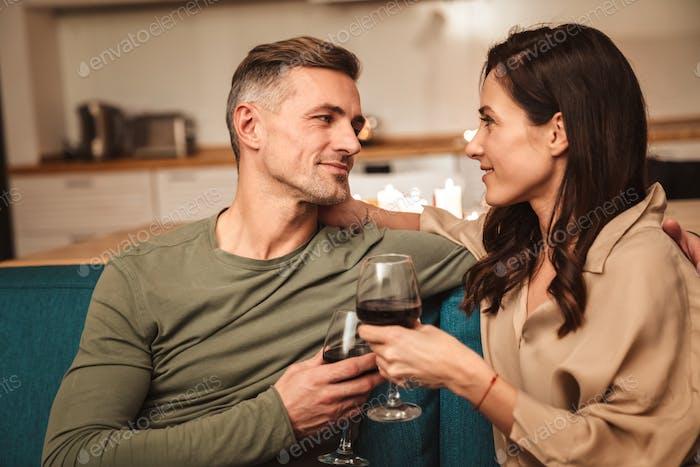 Bild des Paares, das Rotwein trinkt, während romantisches Abendessen zu Hause