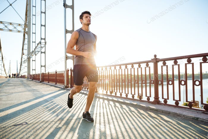 Attractive fit man running along bridge at sunset light