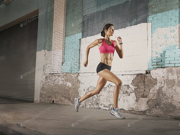 A woman running along an urban street past buildings with peeling paint and a metal shutter.