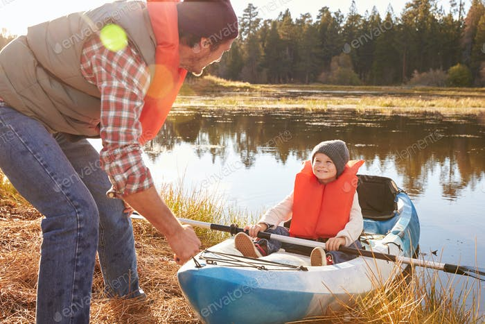 Father preparing launch for son in kayak on lakeside