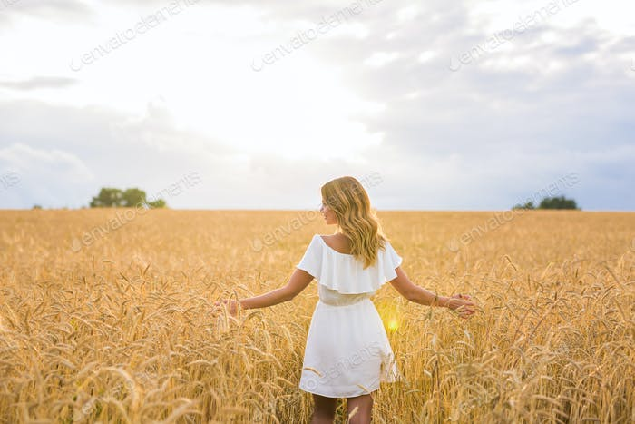 Woman with arms outstretched in a wheat field