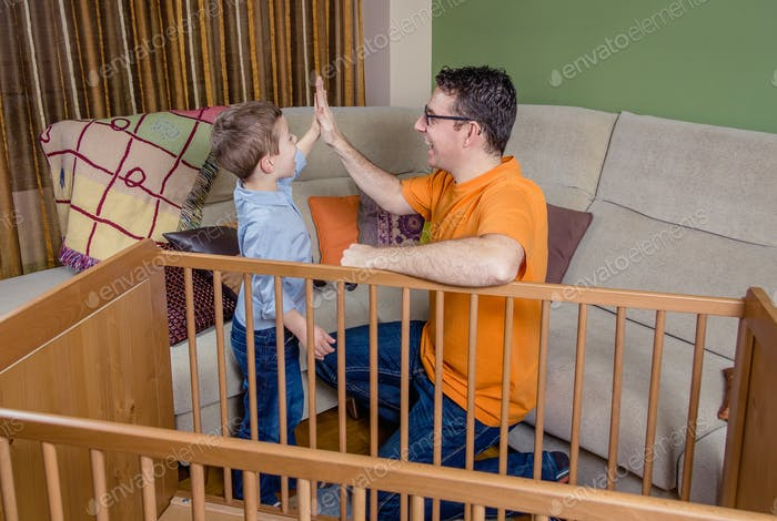 Father and son giving five for success in a home work
