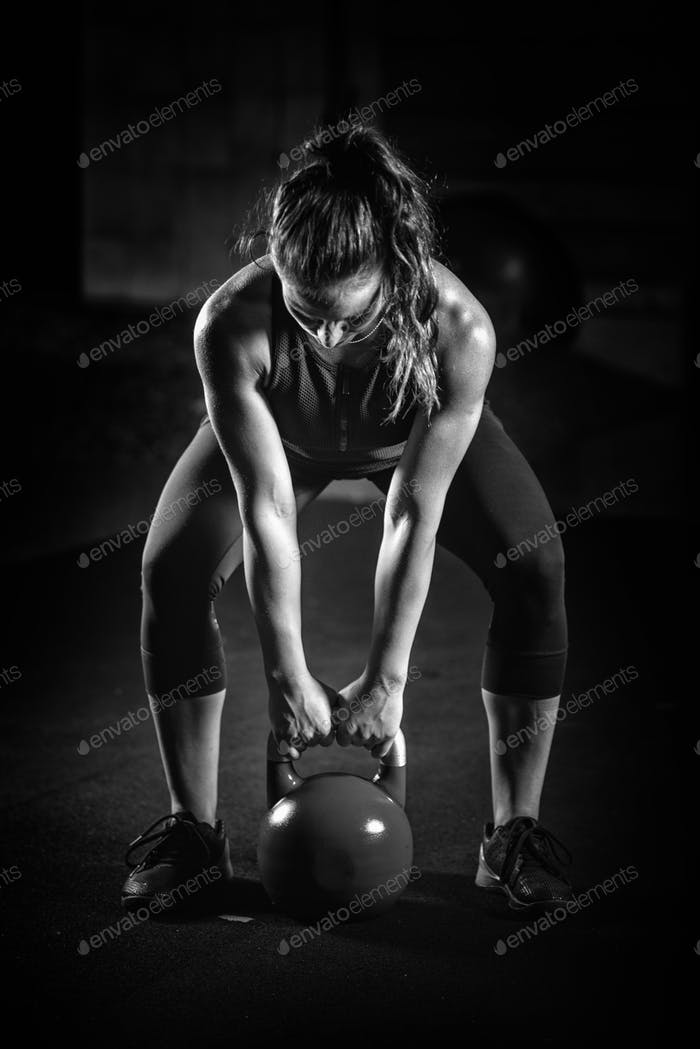 Woman athlete exercising with kettlebell