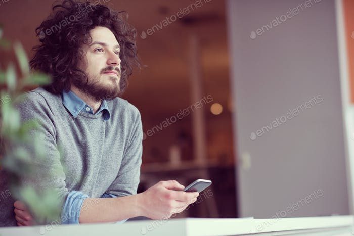 Young casual businessman holding smartphone