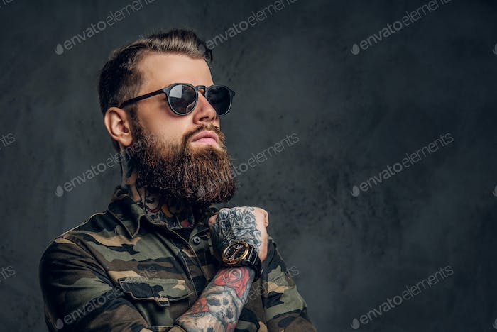 Portrait of a stylish bearded guy with tattooed hands in the military shirt