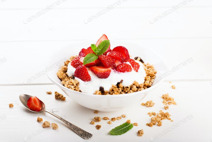 Fresh strawberries , yogurt and homemade granola