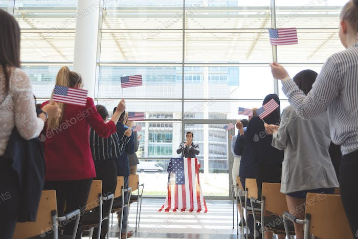 Business people moving american flag in a business seminar in office building