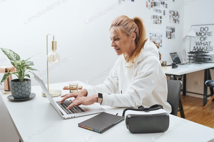 Serious woman types on laptop in comfortable and modern office