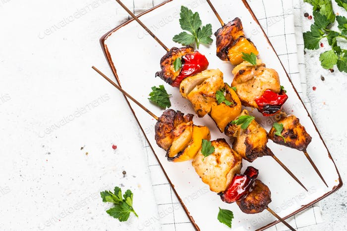 Chicken kebab on skewers on white