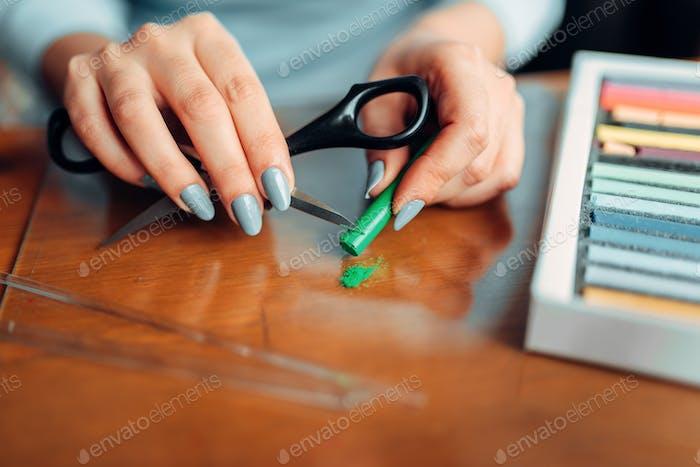 Weibliche Hände halten Schere und grüner Polymer-Ton