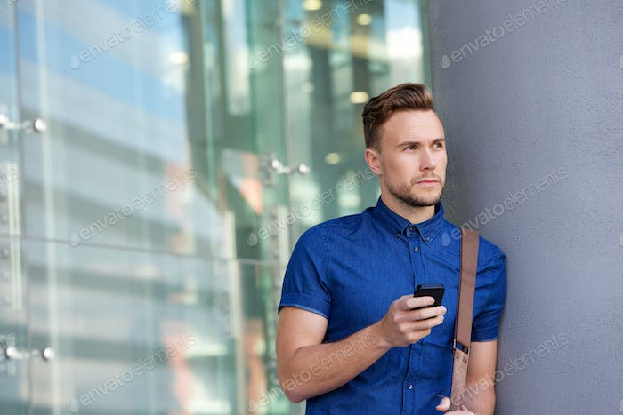 handsome young man leaning against wall outside with cellphone