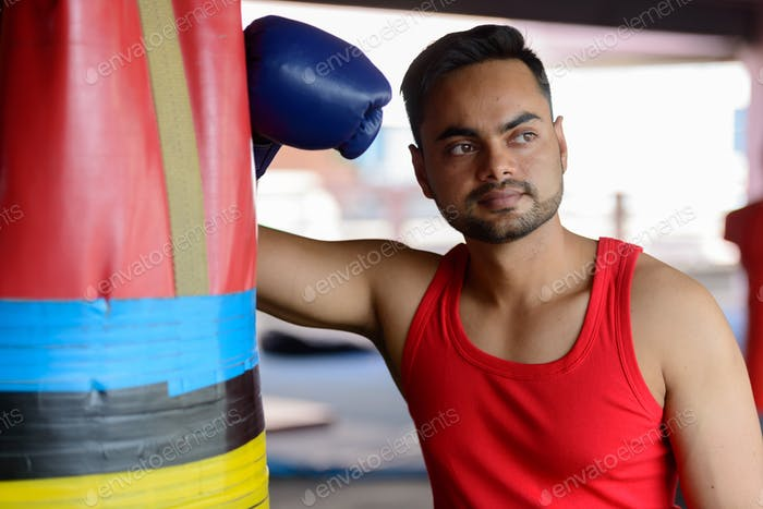 Young bearded Indian man as boxer thinking at the gym