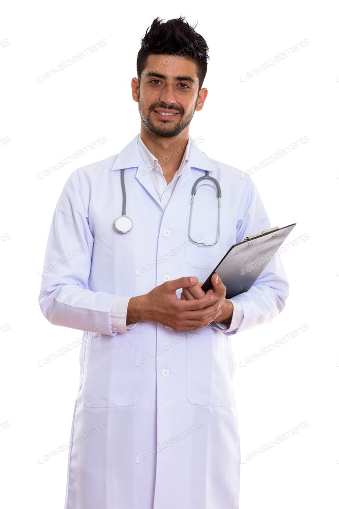 Portrait of young handsome bearded Persian man doctor holding clipboard