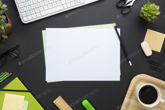Blank Paper Surrounded By Office Equipment On Gray Desk