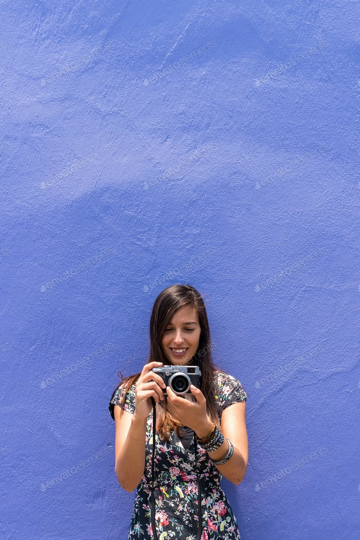 Frau in einem Kleid vor einer bunten Wand in Mexiko