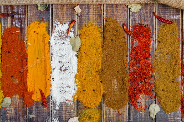 Colourful spices on the table. Various Spices in on wooden background, top view. Spices background