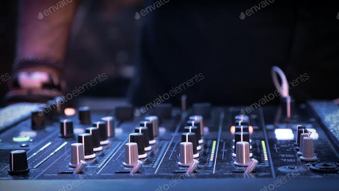 DJ mixer at night in club