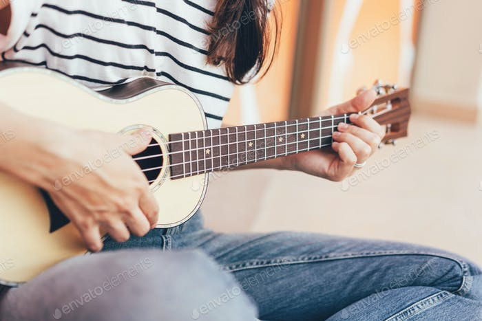Woman play a song on ukulele,  close-up musical instrument.