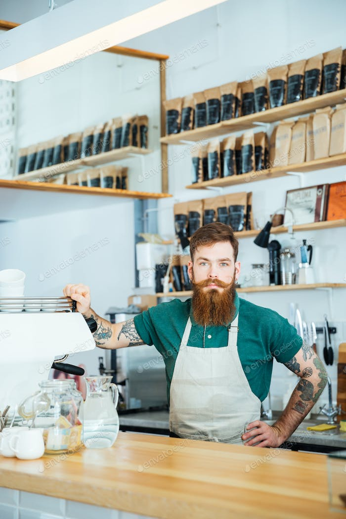Bearded barista with tattooed hands in coffee shop
