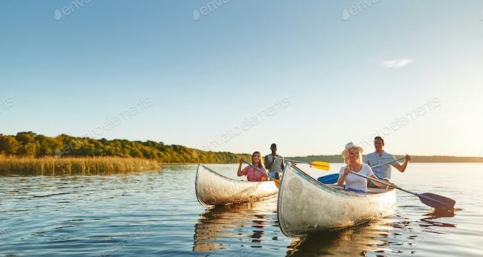 Smiling young friends canoeing together on a lake in summer