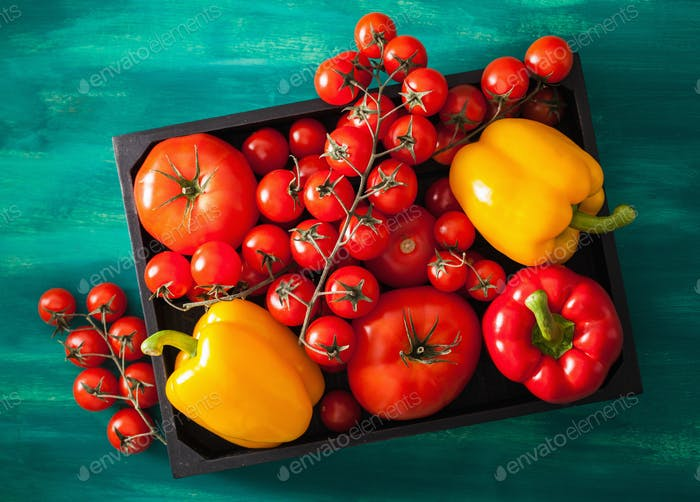 assorted tomatoes and bell peppers in wooden box