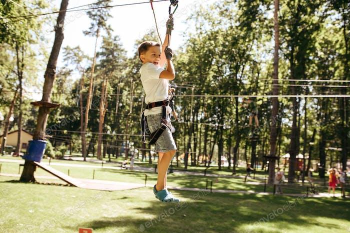 Little brave boy on zipline in rope park
