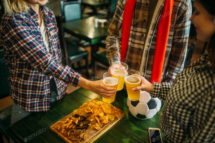 Fußballfans klinken Gläser mit Bier in Sportbar