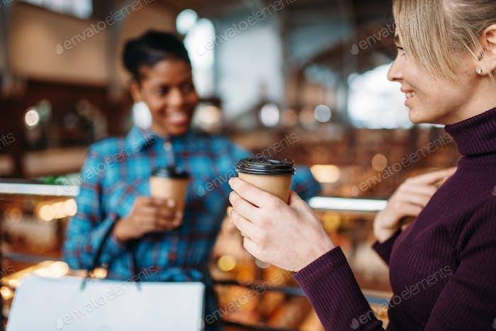 Zwei Freundinnen trinken Kaffee nach dem Einkaufen