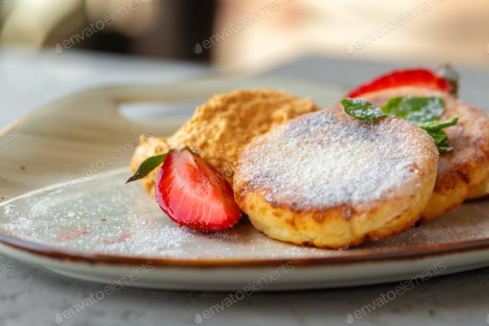 Cottage cheese pancakes with strawberry and sugar powder