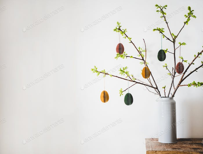 Easter holiday tree branches with festive eggs, copy space