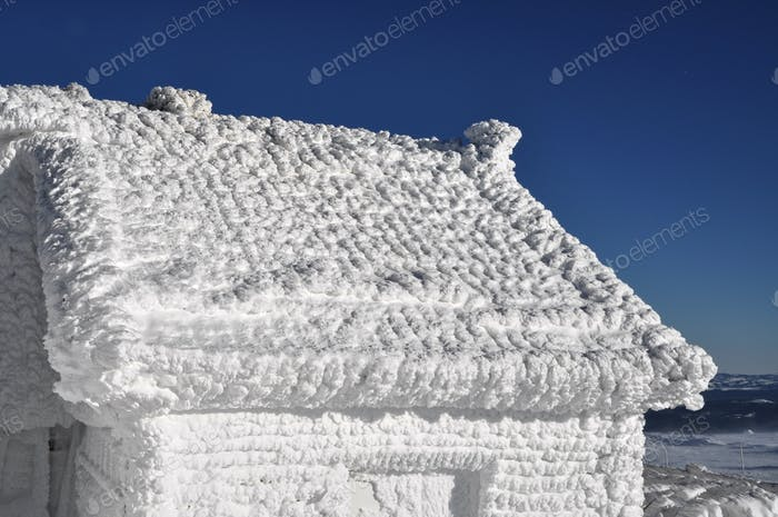 Ice covered house after heavy snowfall and blizzard