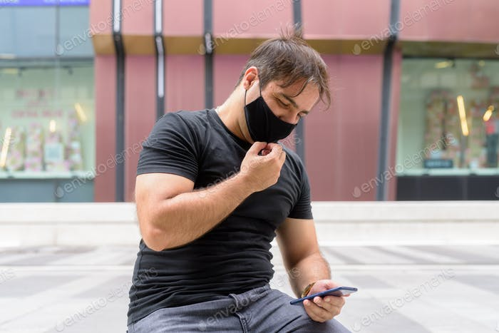Portrait of Persian man with mask using phone and sitting in the city outdoors