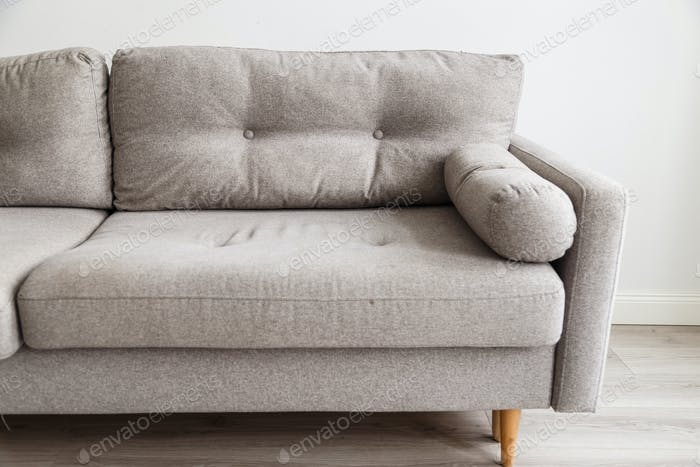 Grey sofa with wooden legs in monochromatic living room