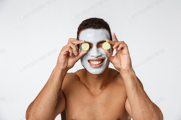 Photo of joyful african american man in facial cosmetic mask making fun with cucumber isolated over