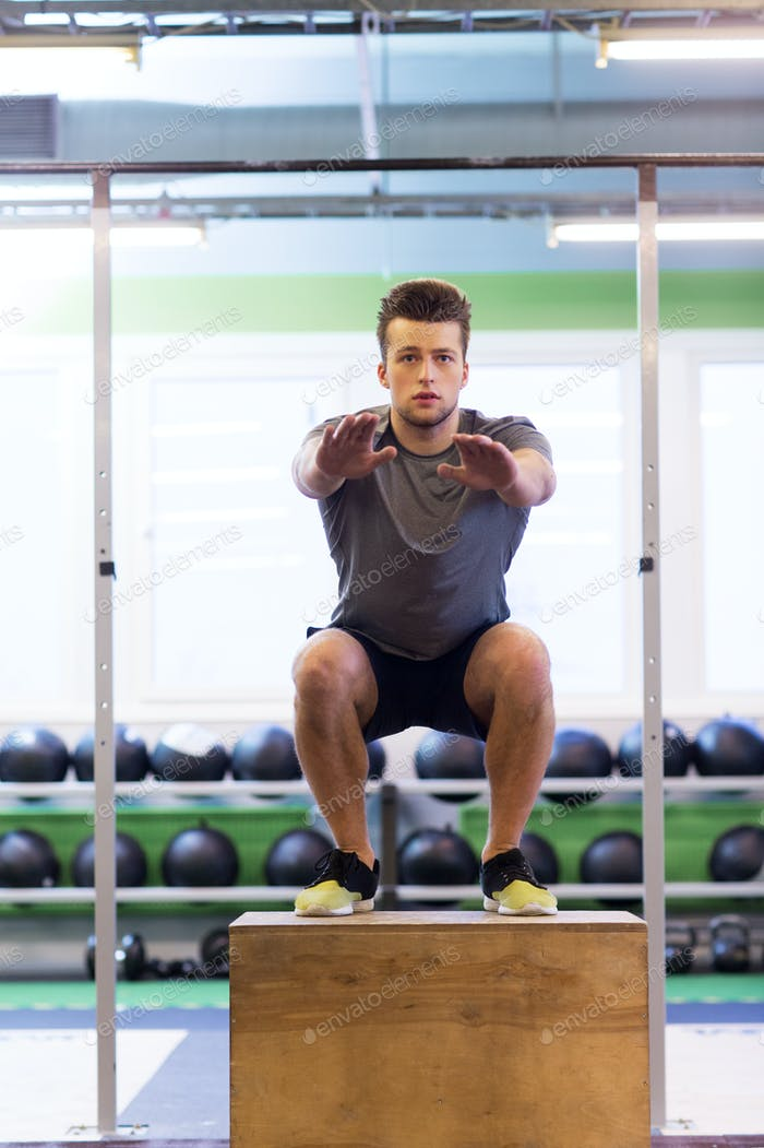 young man doing box jumps exercise in gym