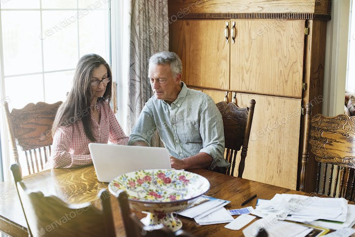 Senior couple sitting at a dining table, using a laptop computer, paperwork and bills on the table.