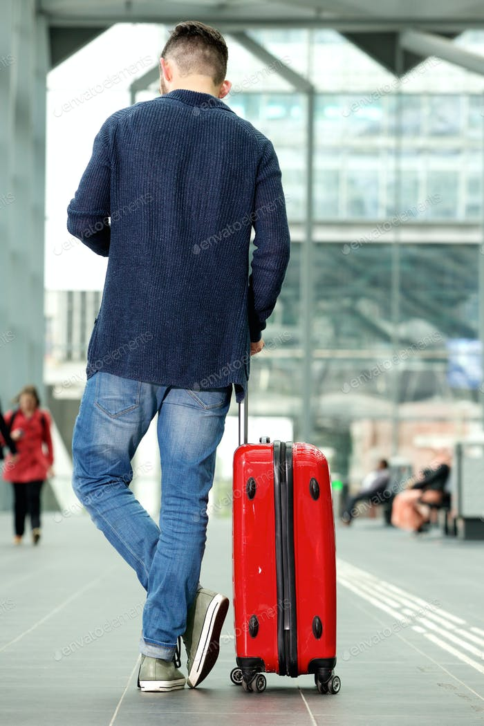 Man standing in airport with travel bag