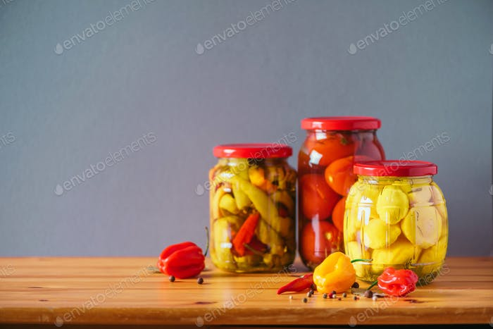 Preserved vegetables in glass jars on wooden background. Copy space. Healthy fermented food concept